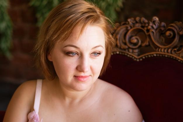 古い栗色のベルブの背景にブロンドの髪のクローズアップと大人の青い目の女性の肖像画...