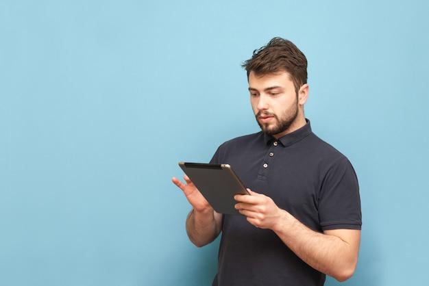 大人の男性の肖像画は、ひげと暗いtシャツを着て、タブレットでインターネットを使用しています。