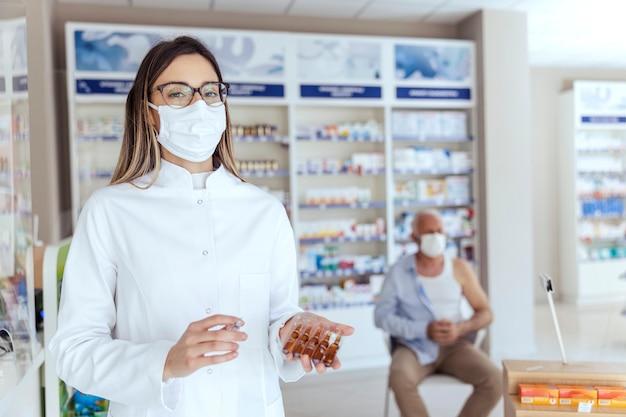 手にワクチンを持って薬局の真ん中に立っている大人の女性看護師の肖像画