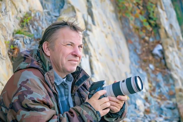 Портрет взрослого туриста-фотографа-мужчины с фотоаппаратом в руках с задумчивым взглядом на природе, образ жизни туристического фотографа