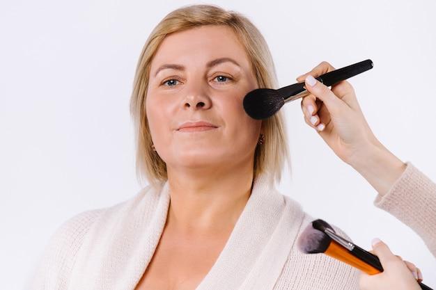 Портрет взрослой женщины и руки мастера, которые делают макияж кистью на белом фоне студии. фото высокого качества