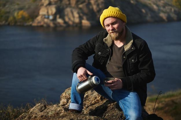 Портрет авантюриста в желтой вязаной шерстяной шапке и в джинсах, сидящего на камнях, держащего термос, наливающего в чашку теплый напиток и отдыхающего во время прогулки на природе.