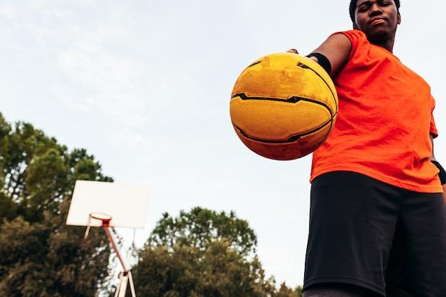 도시 농구 코트에 농구를 들고있는 아프리카 계 미국인 흑인 소년의 초상화. 오렌지색 티셔츠를 입고.