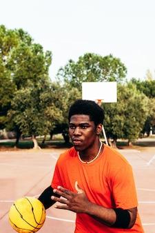 Портрет афро-американского темнокожего мальчика, играющего в баскетбол на городской площадке.