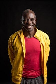 カメラを見て笑って立っているアフリカ系アメリカ人の男の肖像画