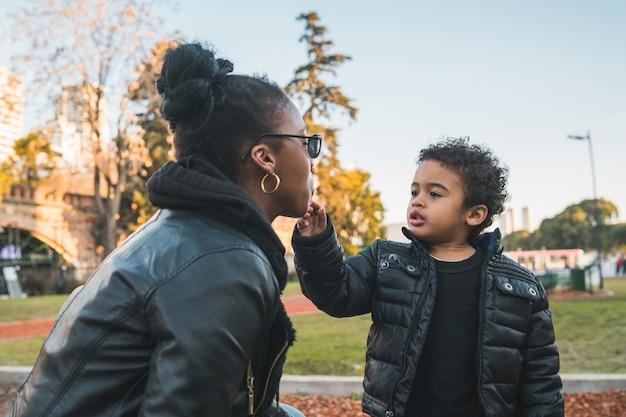 公園で屋外に立って楽しんでいる息子とアフリカ系アメリカ人の母親の肖像画。一人親家庭。