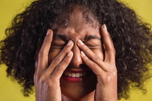 그녀의 눈을 감고 그녀의 얼굴에 그녀의 손으로 웃 고 아프리카계 미국인 여자의 초상화.