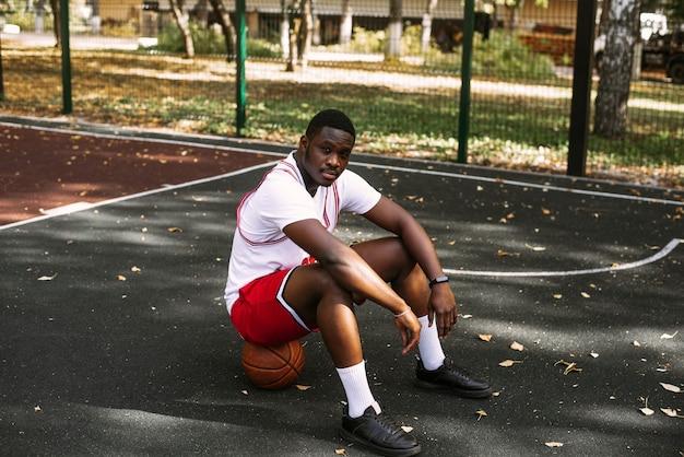 バスケットボールを保持し、バスケットボールコートに座っているアフリカ系アメリカ人の若い男の肖像画。ワークアウト中に休憩してください。ファッショナブルなスポーツの肖像画。
