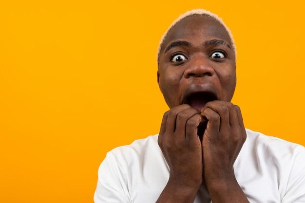 コピースペースと黄色の驚きで口を開けてアフリカの黒人男性の肖像画