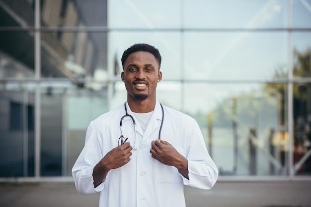 カメラを見て、クリニックの前で笑っているアフリカの医師の肖像画