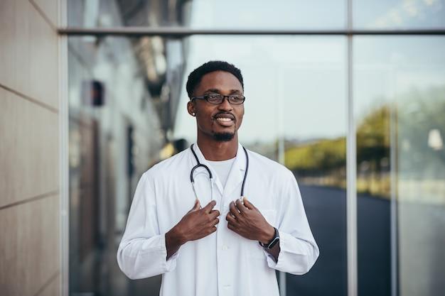 Портрет африканского врача, смотрящего в камеру и улыбающегося перед клиникой