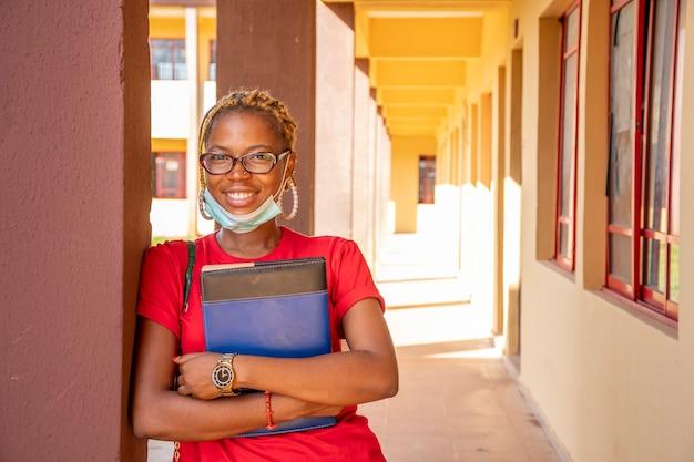 フェイスマスクで笑っているアフリカの女子学生の肖像画が勝ちました