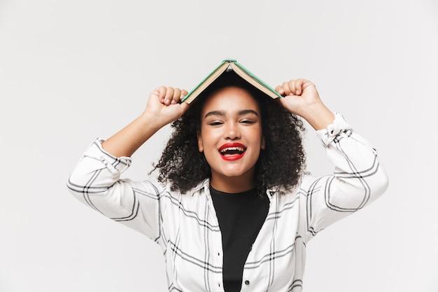 Портрет африканской женщины, стоящей изолированно на белом фоне с книгой на голове