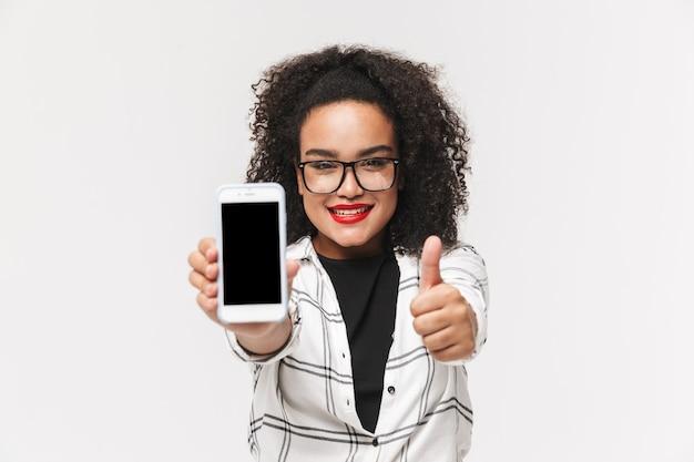 白い背景の上に孤立して立っているアフリカの女性の肖像画、空白の画面の携帯電話を表示、親指を立てる