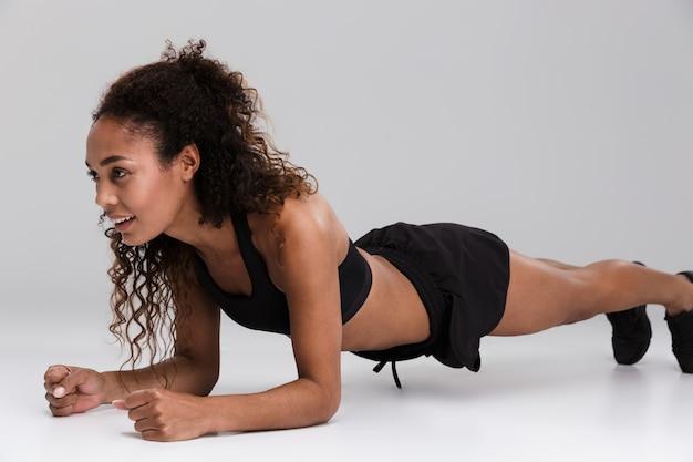 회색 배경 위에 절연 판자 운동을 하 고 아프리카 미국 젊은 웃는 sportswoman의 초상화