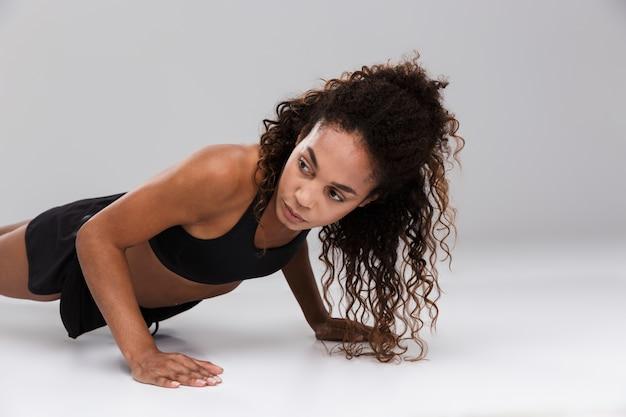 회색 배경 위에 절연 판자 운동을 하 고 아프리카 미국 젊은 강한 sportswoman의 초상화
