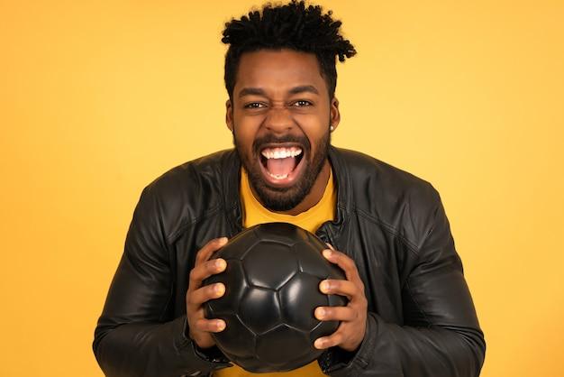고립 된 배경에 축구 공을 들고 흥분 찾고 아프리카 남자의 초상화. 스포츠 개념입니다.