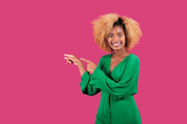 Портрет афро женщины, улыбающейся и указывающей в сторону, стоя на красочном фоне. концепция рекламы и продвижения.