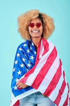 선글라스를 끼고 고립된 배경 위에 미국 국기로 싸여 웃고 있는 아프리카 여성의 초상화.