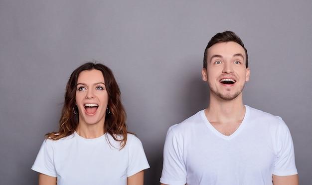 基本的な白い t シャツを着た、驚いたカップルの男女のポートレート