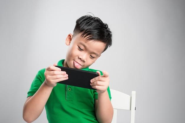 分離されたスマートフォンでゲームをしている面白がってかわいい小さな子供の肖像画