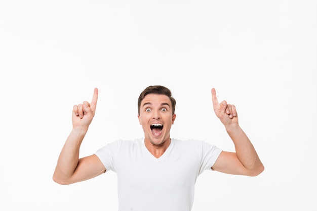 Портрет удивленного возбужденного мужчины в белой футболке