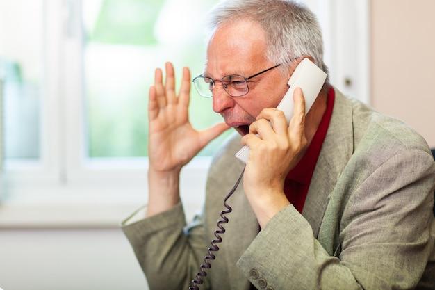 Портрет разгневанного бизнесмена, кричащего по телефону