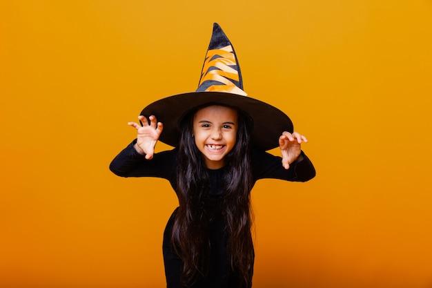 노란색 배경에 마녀 의상을 입은 화난 어린 소녀의 초상화. 할로윈.