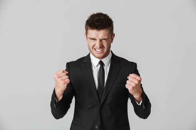 Портрет сердитого молодого бизнесмена в костюме