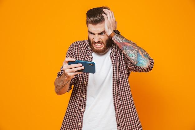 Портрет разгневанного молодого человека в повседневной одежде, играющего в игры на мобильном телефоне
