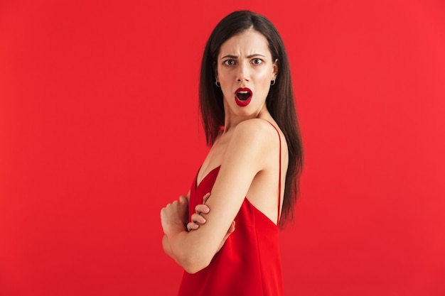 Портрет сердитой молодой женщины в изолированном платье, взявшись за руки сложенными