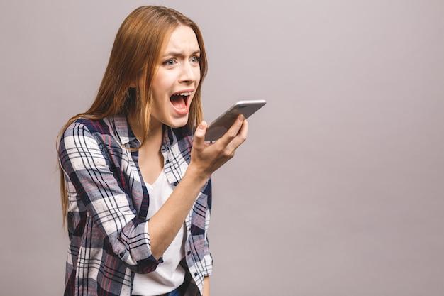회색 벽에 고립 된 휴대 전화 소리 화가 젊은 여자의 초상화.