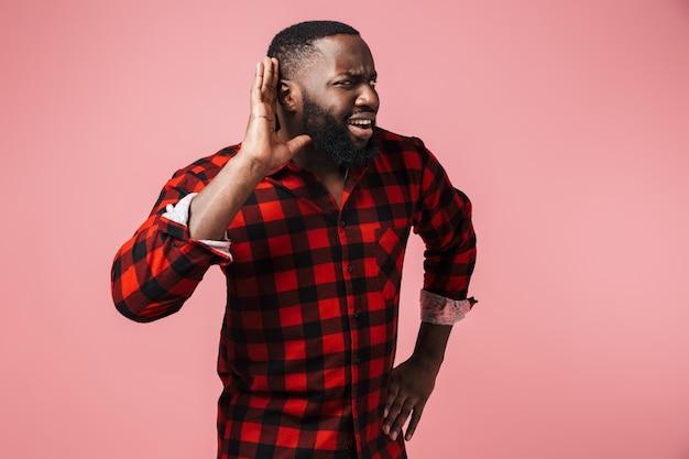 Портрет раздраженного африканца в клетчатой рубашке, стоящего изолированно над розовой стеной, жестикулирующего и пытающегося услышать новости