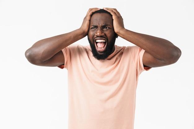 Портрет раздраженного африканца в футболке, стоящего изолированно над белой стеной и страдающего головной болью