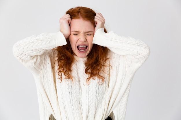 Портрет раздраженной молодой рыжеволосой девушки, стоящей изолированно на белом фоне и страдающей от головной боли