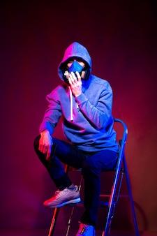 匿名の男の肖像画、暗い背景の上にネオンマスクを身に着けているハッカー。ネオン照明の近くで銃を持っている異人種間のサイバーパンクプレーヤーの選択的な焦点
