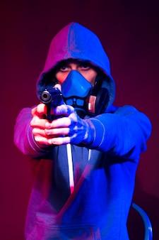 Портрет анонимного человека, хакера в неоновой маске на темном фоне. избирательный фокус двухрасового киберпанк-игрока, держащего оружие возле неонового освещения