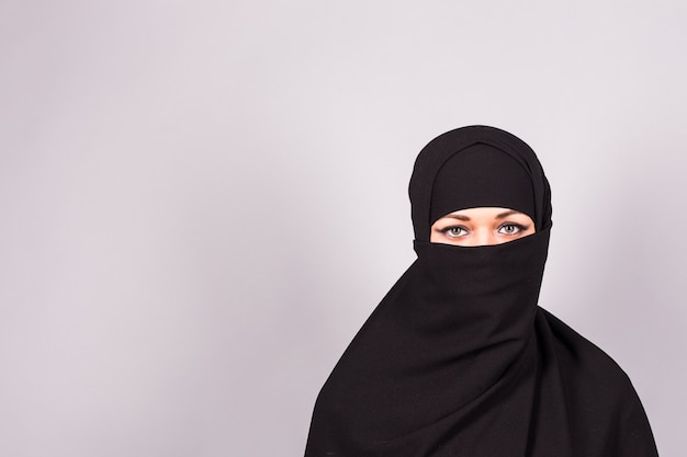 전통적인 이슬람 천으로 niqab에서 그녀의 아름다운 파란 눈을 가진 아랍 젊은 여자의 초상화.