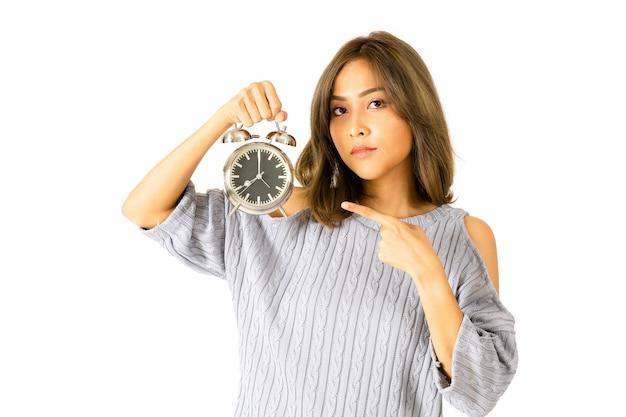 怒っているアジアの怒っている女性の肖像画と目覚まし時計で彼女の指を指す