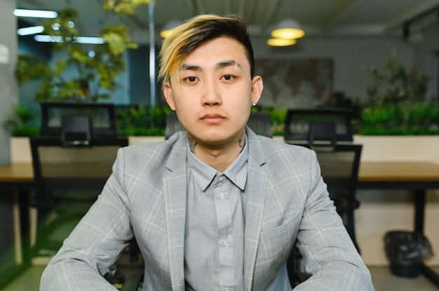 Портрет азиатского бизнесмена, смотрящего на фото высокого качества видеоконференции камеры