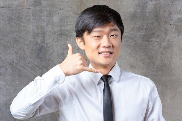 Портрет азиатского бизнесмена, показывающего символ «позвони мне»