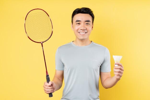 Портрет азиатского мужчины, держащего ракетку для бадминтона на желтой стене