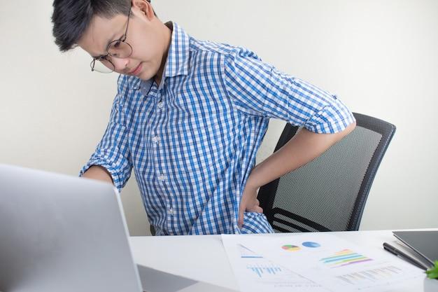 オフィスで働いている間に背中の痛みと格子縞のシャツを着ているアジア人の肖像画。オフィス症候群。