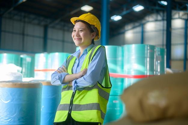Портрет азиатской улыбающейся инженерной женщины работает на современном складе