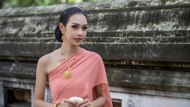 タイの伝統的なダンサーの服のアジアの女性の肖像画は、古代の仏像に対して立っています。アユタヤ歴史公園、タイアジア。