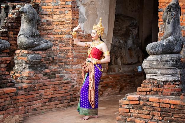 タイの伝統的なダンサーの服のアジアの女性の肖像画は、古代の仏像に対して立っています。アユタヤ歴史公園、タイ