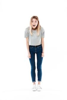 Портрет изумленной милой молодой женщины стоя с раскрытым ртом