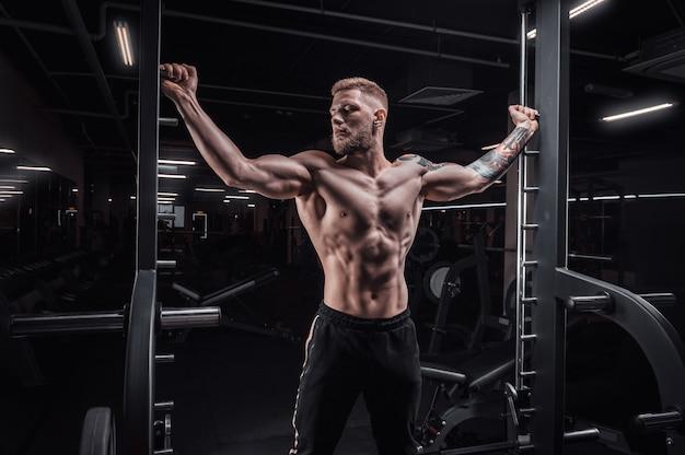 Портрет спортсмена у специальной рампы в спортзале. бодибилдинг и фитнес-концепция. смешанная техника