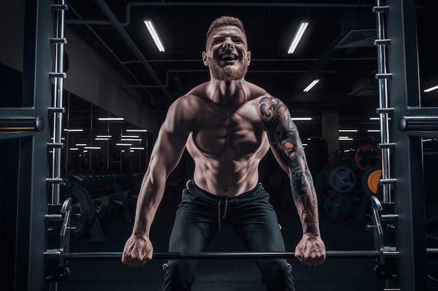 Портрет спортсмена, выполняющего становую тягу в тренажерном зале. бодибилдинг и фитнес-концепция. смешанная техника