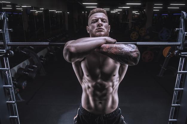 Портрет спортсмена, выполняющего присед со штангой в тренажерном зале. бодибилдинг и фитнес-концепция. смешанная техника
